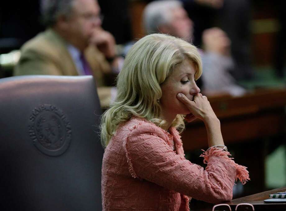 Sen. Wendy Davis, D-FortWorth, sits at her desk after the Texas Senate passes an abortion bill, Friday, July 12, 2013, in Austin, Texas. The bill will require doctors to have admitting privileges at nearby hospitals, only allow abortions in surgical centers, dictate when abortion pills are taken and ban abortions after 20 weeks. Photo: Eric Gay, Associated Press / AP