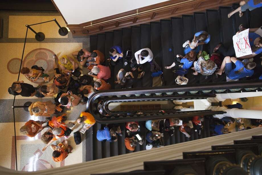 Hundreds wait in line to enter the Senate Gallery at the Texas State Capitol in Austin, Texas on Friday, July 12, 2013. The Texas Senate's leader, Lt. Gov. David Dewhurst, has scheduled a vote for Friday on the same restrictions on when, where and how women may obtain abortions in Texas that failed to become law after a Democratic filibuster and raucous protesters were able to run out the clock on an earlier special session. (AP Photo/Tamir Kalifa) Photo: Tamir Kalifa, Associated Press
