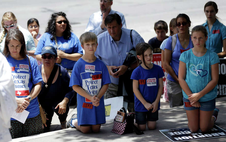 Anti-abortion supporters pray outside the Texas Capitol as the Texas House  debates HB 2, a bill that will place restrictions on abortion in the state, Tuesday, July 9, 2013, in Austin, Texas. (AP Photo/Eric Gay) Photo: Eric Gay, ASSOCIATED PRESS / AP2013
