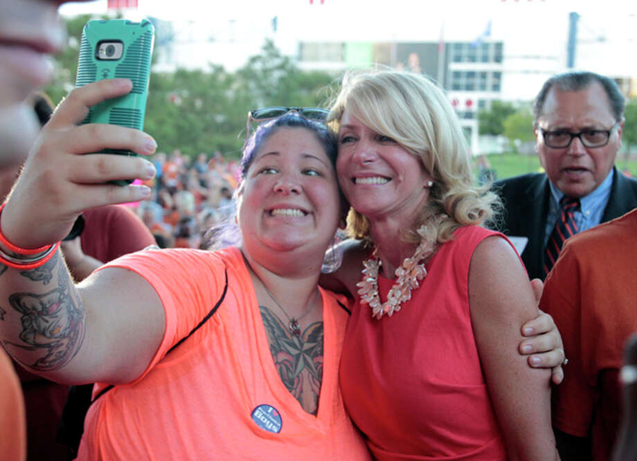 Catherine Arnold, left, of Spring Texas has her photo taken with State Sen. Wendy Davis during the Planned Parenthood Action Fund's Stand with Texas Women Rally at Discovery Green in Houston, Texas. The Rally highlighted the abortion restriction bill, House Bill 2 being Pushed in Austin Tuesday, July 9, 2013, in Houston. (AP Photo/Houston Chronicle, Billy Smith II) Photo: Billy Smith II, ASSOCIATED PRESS / 2013 HOUSTON CHRONICLE2013