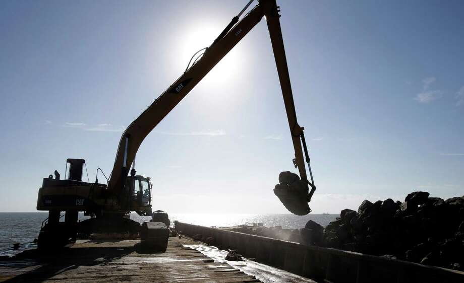 A large excavator is silhouetted as it scoops up a load of limestone boulders from a barge in the gulf of Mexico off the Texas coast on Tuesday, Oct. 29, 2013. The huge boulders will be dropped into the water to help rebuild a reef that once filled some 400 acres and now barely exists. Photo: Pat Sullivan, AP / AP