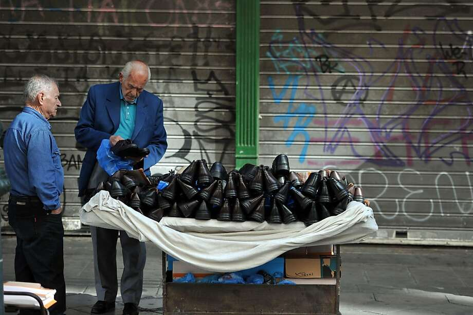 Special today - buy a right shoe, get the left free!A street vendor tries to make a sale in central Athens. Photo: Louisa Gouliamaki, AFP/Getty Images