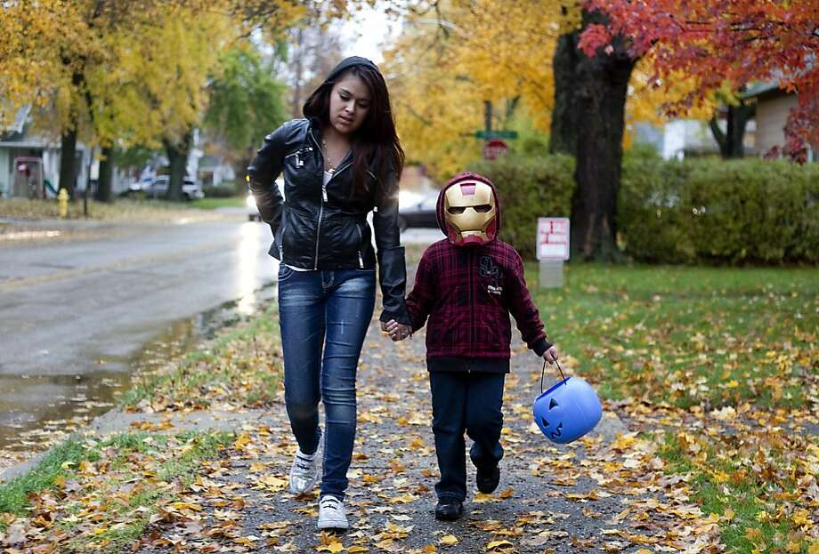 A good big sister: Adrea Gonzalez decided to go into work late so she could take her 4-year-old brother, Jovany, trick-or-treating in Goshen, Ind. Hope she didn't get fired. Photo: Jon Garcia, Associated Press