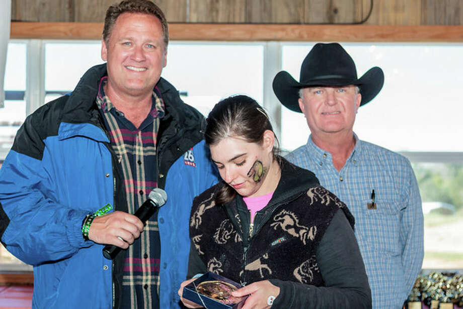 Don Teague of Fox26 after presenting Trail Boss award to SIRE rider Alexandra Dumas. Representative of title sponsor CGG, Don Parson, stands on right. Photo: Photo Provided By SIRE / James Pharaon Creative