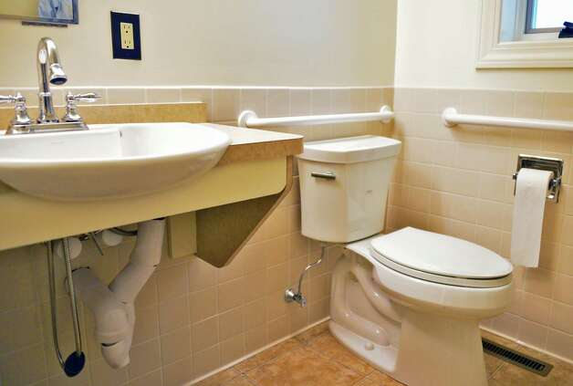 handicap accessible bathroom with grab rails as towel racks in the