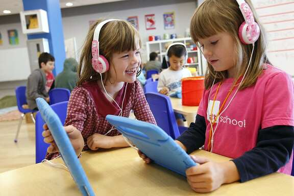 Fiona, 5, left, shows Lina, 5, a picture on her iPad as they work on a lesson during class at Alt School in San Francisco, CA Friday, October 25, 2013. Alt School was founded by techie Max Ventilla, and uses a start-up mentality towards building a home-schooled environment for children to learn in