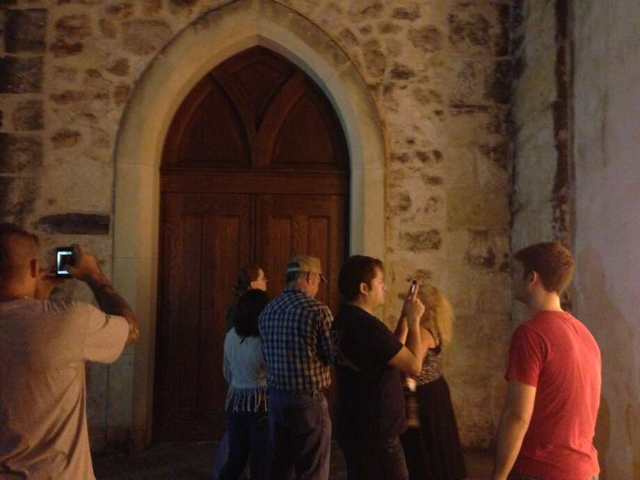 Tour attendees try to capture spirits along the side of San Fernando Cathedral. Photo: Benjamin Olivo, MySA.com