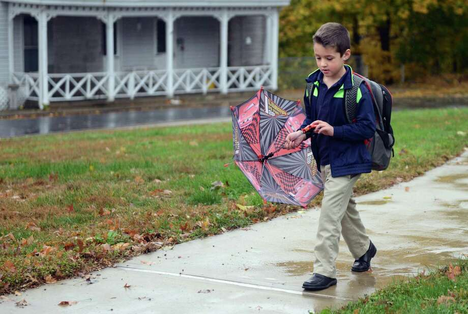 Six-year-old Richie Curry, a first-grade student at St. Joseph School in Shelton, Conn., walks through a puddle after getting out of school early on Friday, Nov. 1, 2013. A quick moving cold front brought strong winds and some rain to southwestern Connecticut late Friday morning, with gusts to nearly 30 mph, but the sky brightened by mid-afternoon. Photo: Autumn Driscoll / Connecticut Post
