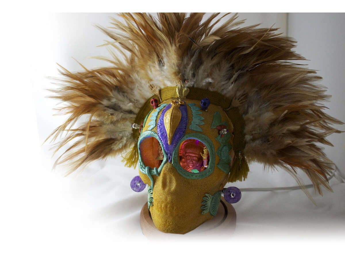 An Aztec- style skull features a feather headdress and milagros (charms) dangling in the eye sockets.