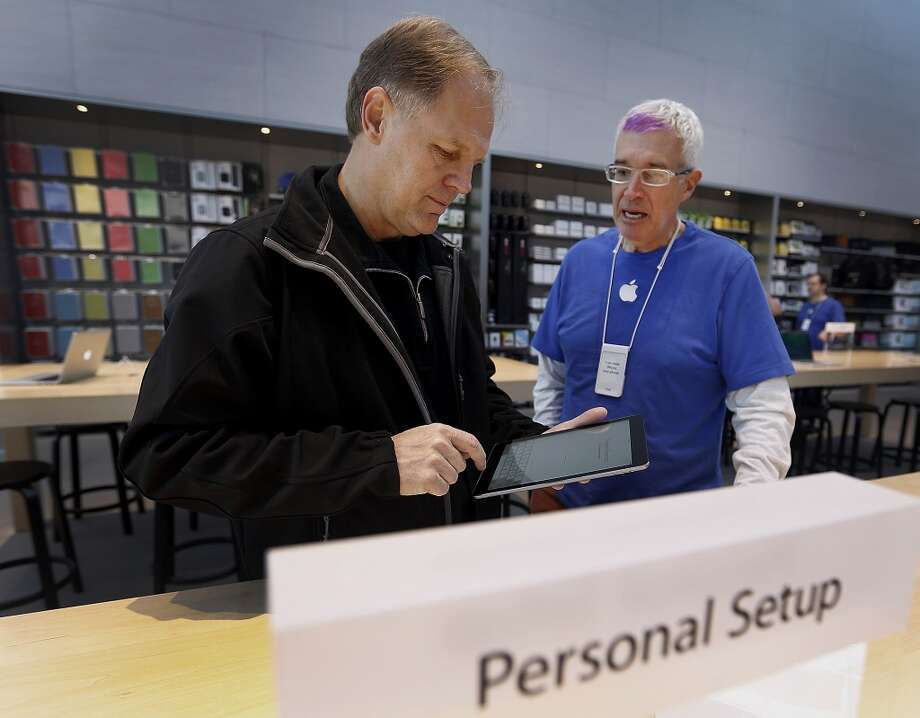 Customer Dale Scott, left, gets help from an employee with setting up a new Apple Inc. iPad Air at a store in Palo Alto, California, U.S., on Friday, Nov. 1, 2013. Apple Inc.'s forecast for the slowest holiday sales growth in a half decade reflects how iPhones and iPads aren't providing the growth surges they once did as competition accelerates in the saturated mobile market. Photographer: Tony Avelar/Bloomberg *** Local Caption *** Dale Scott Photo: Tony Avelar, Bloomberg
