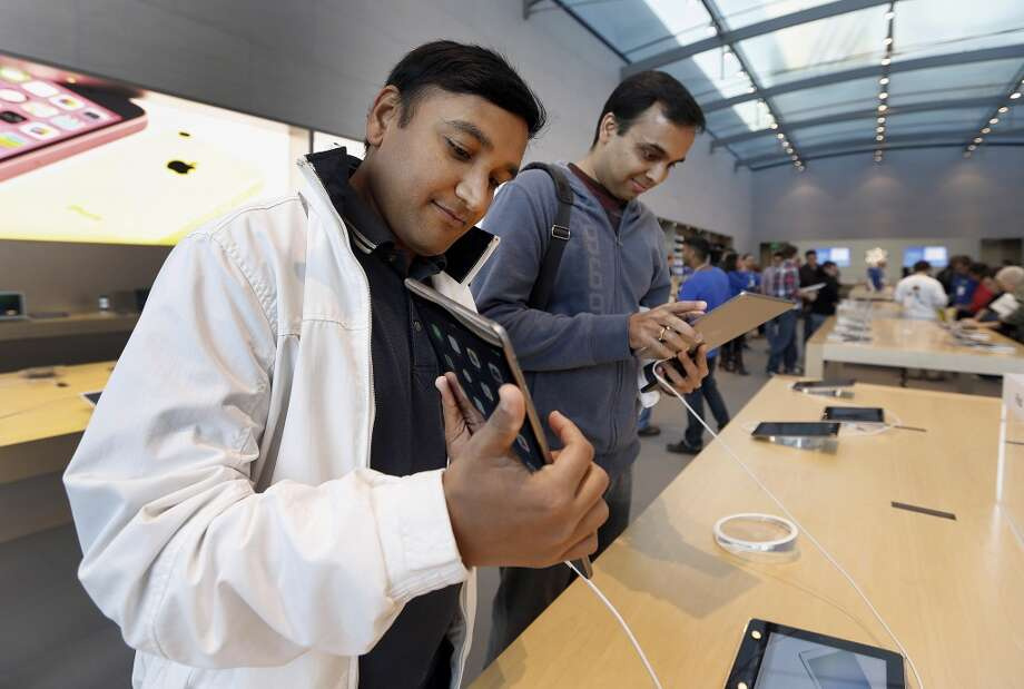 Customers Anand Inani, left, and Sanjith Thayyilthodiyil check out the new Apple Inc. iPad Air on the first day of sales of the at a store in Palo Alto, California, U.S., on Friday, Nov. 1, 2013. Apple Inc.'s forecast for the slowest holiday sales growth in a half decade reflects how iPhones and iPads aren't providing the growth surges they once did as competition accelerates in the saturated mobile market. Photographer: Tony Avelar/Bloomberg *** Local Caption *** Anand Inani; Sanjith Thayyilthodiyil Photo: Tony Avelar, Bloomberg