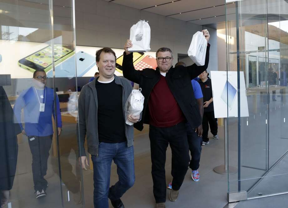 Customers walk out with new iPad Airs on Friday, Nov. 1, 2013, in Stanford, Calif. Apple's iPad Air, a thinner, lighter and faster-running version of its previous large tablet computers, goes on sale Friday with a starting price of $499. The company also unveiled an updated version of its iPad Mini recently. It goes on sale sometime in November. (AP Photo/Marcio Jose Sanchez) Photo: Marcio Jose Sanchez, Associated Press