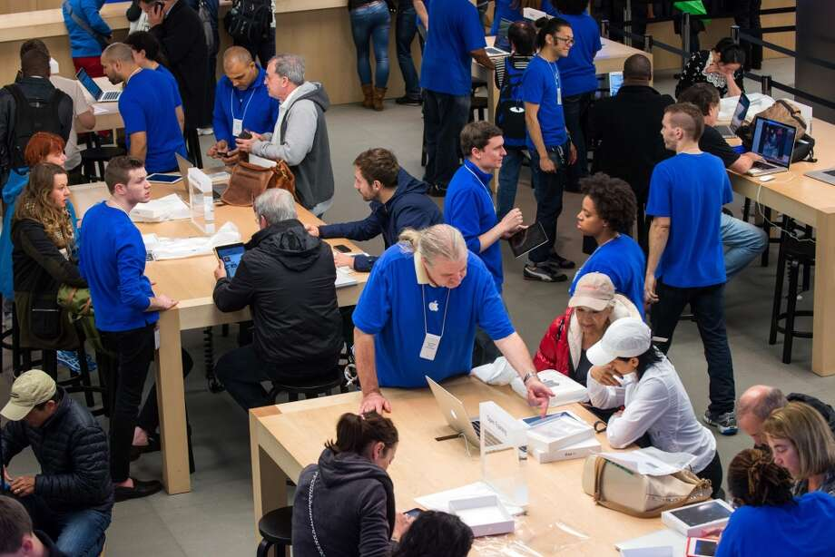 Apple Inc. employees help shoppers on the first day of sales of the new iPad Air at the 5th Avenue Apple store in New York, U.S., on Friday, Nov. 1, 2013. Apple Inc.'s forecast for the slowest holiday sales growth in a half decade reflects how iPhones and iPads aren't providing the growth surges they once did as competition accelerates in the saturated mobile market. Photographer: Craig Warga/Bloomberg Photo: Craig Warga, Bloomberg