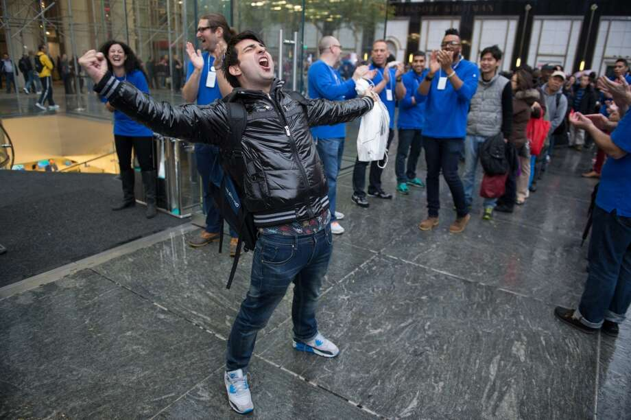 Rami Shamis celebrates after being the first to buy the new Apple Inc. iPad Air at the 5th Avenue Apple store in New York, U.S., on Friday, Nov. 1, 2013. Apple Inc.'s forecast for the slowest holiday sales growth in a half decade reflects how iPhones and iPads aren't providing the growth surges they once did as competition accelerates in the saturated mobile market. Photographer: Craig Warga/Bloomberg *** Local Caption *** Rami Shamis Photo: Craig Warga, Bloomberg