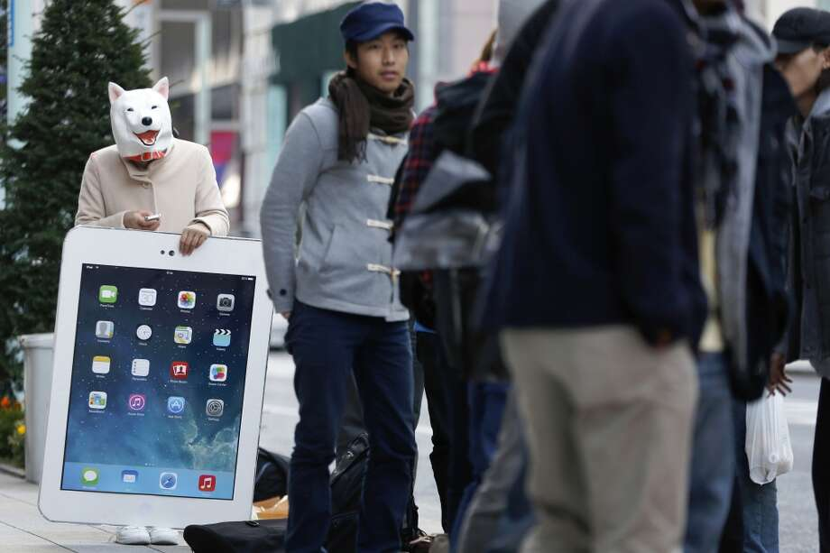 A woman, wearing a dog mask, uses a mobile device while holding a giant cardboard copy of an iPad as she waits in line with other customers outside an Apple Inc. store ahead of the launch of the company's iPad Air in the Ginza district of Tokyo, Japan, on Friday, Nov. 1, 2013. Apple Inc.'s forecast for the slowest holiday sales growth in a half decade reflects how iPhones and iPads aren't providing the growth surges they once did as competition accelerates in the saturated mobile market. Photographer: Kiyoshi Ota/Bloomberg Photo: Kiyoshi Ota, Bloomberg