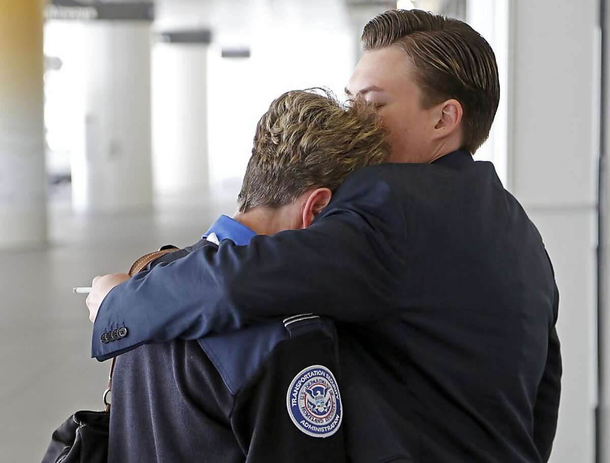 Transportation Security Administration employees hug outside Terminal 1 at Los Angeles International Airport on Friday, Nov. 1, 2013. A gunman armed with a semi-automatic rifle opened fire at Los Angeles International Airport on Friday, killing a Transportation Security Administration employee and wounding two other people. Flights were disrupted nationwide.