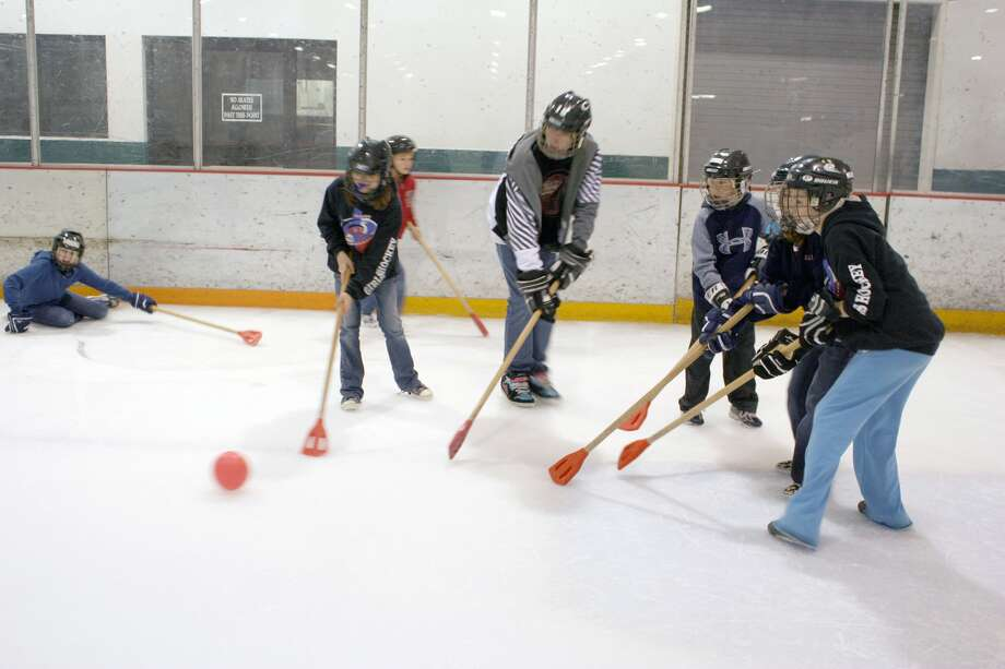 """Broom BallThe game originated in Canada. Two teams of six run around the ice and try to get the ball into the other team's net. It's pretty much hockey except instead of skates the players wear special rubber shoes, use a ball instead of a puck, and they use a """"broom"""" with a wooden or aluminum shaft and a rubber-molded triangular head to move the ball around."""