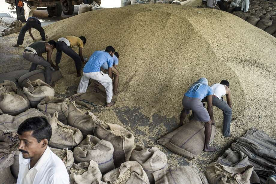 India: Day laborers pack soybeans into gunny sacks at a grain market in Burhanpur, Madhya Pradesh, India. India's soybean output estimates have been cut to 12.2m tons, from 12.98m tons, for the monsoon-sown harvest as excess rains affect yields. Photo: Sanjit Das, Bloomberg