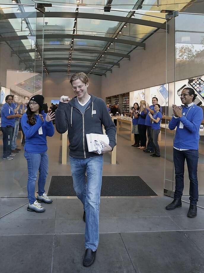 Customer Noah Wasmer smiles while walking out with a new Apple Inc. iPad Air on the first day of sales at a store in Palo Alto, California, U.S., on Friday, Nov. 1, 2013. Apple Inc.'s forecast for the slowest holiday sales growth in a half decade reflects how iPhones and iPads aren't providing the growth surges they once did as competition accelerates in the saturated mobile market. Photographer: Tony Avelar/Bloomberg *** Local Caption *** Noah Wasmer Photo: Tony Avelar, Bloomberg