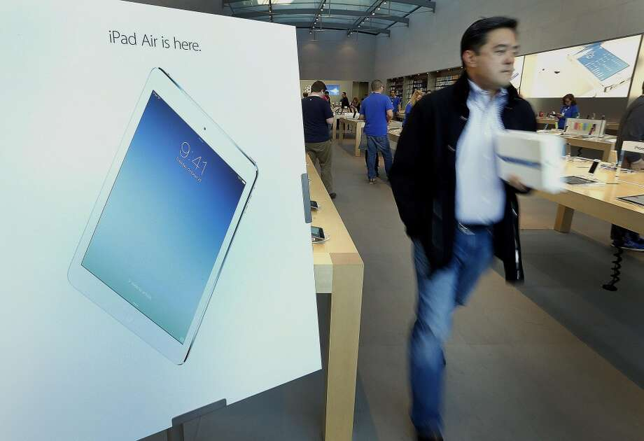 An advertisement for the new Apple Inc. iPad is displayed as a customer exits a store in Palo Alto, California, U.S., on Friday, Nov. 1, 2013. Apple Inc.'s forecast for the slowest holiday sales growth in a half decade reflects how iPhones and iPads aren't providing the growth surges they once did as competition accelerates in the saturated mobile market. Photographer: Tony Avelar/Bloomberg Photo: Tony Avelar, Bloomberg