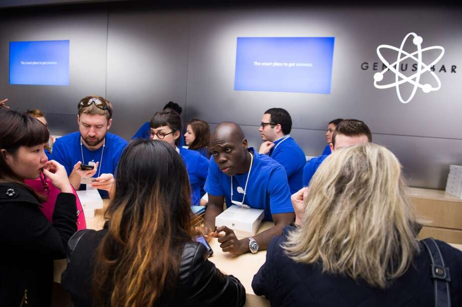 Apple Inc. employees help shoppers purchase the new iPad Air on the first day of sales at the 5th Avenue Apple store in New York, U.S., on Friday, Nov. 1, 2013. Apple Inc.'s forecast for the slowest holiday sales growth in a half decade reflects how iPhones and iPads aren't providing the growth surges they once did as competition accelerates in the saturated mobile market. Photographer: Craig Warga/Bloomberg Photo: Craig Warga, Bloomberg