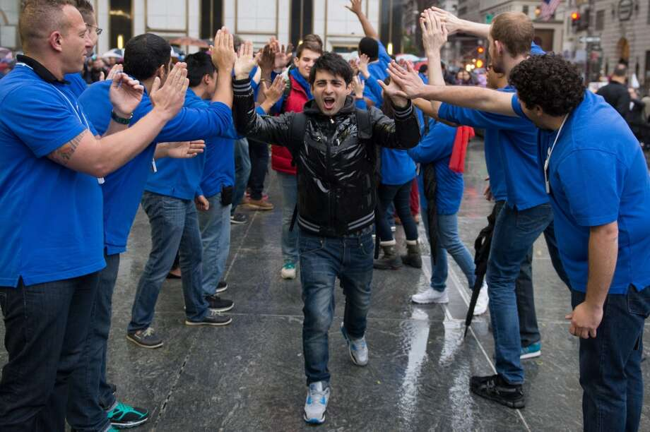 Apple Inc. employees give high fives to Rami Shamis for being first in line to buy the new iPad Air at the 5th Avenue Apple store in New York, U.S., on Friday, Nov. 1, 2013. Apple Inc.'s forecast for the slowest holiday sales growth in a half decade reflects how iPhones and iPads aren't providing the growth surges they once did as competition accelerates in the saturated mobile market.  Photographer: Craig Warga/Bloomberg *** Local Caption *** Rami Shamis Photo: Craig Warga, Bloomberg