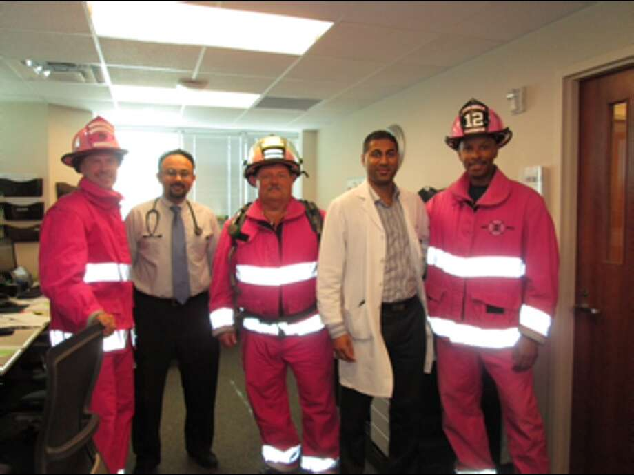 In honor of Breast Cancer Awareness Month, the Pink Heals Tour made a pit stop in Katy on Friday, Oct. 25, at the MD Anderson Regional Care Center. Dr. Sunil Patel, left, and Dr. Nikesh Jasani, right, gave the pink responders a tour of the facility. Photo: MD Anderson Regional Care Center
