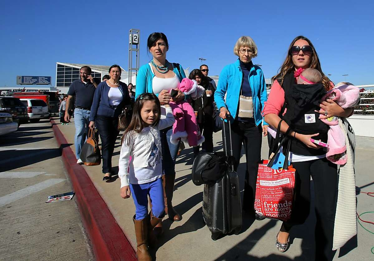 Passengers evacuate the Los Angeles International Airport on Friday Nov. 1, 2013, after shots were fired there, prompting authorities to evacuate a terminal and stop flights headed for the city from taking off from other airports.