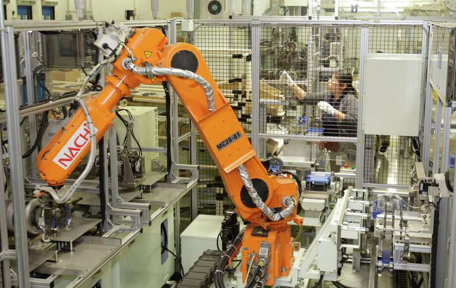 A robotic arm moves parts from one area to another for assembly in Toshiba's plant at 13131 West Little York. The devices made at the Houston factory are installed in hybrid and electric cars made by Ford in Michigan. Photo: Melissa Phillip, Staff / © 2013  Houston Chronicle