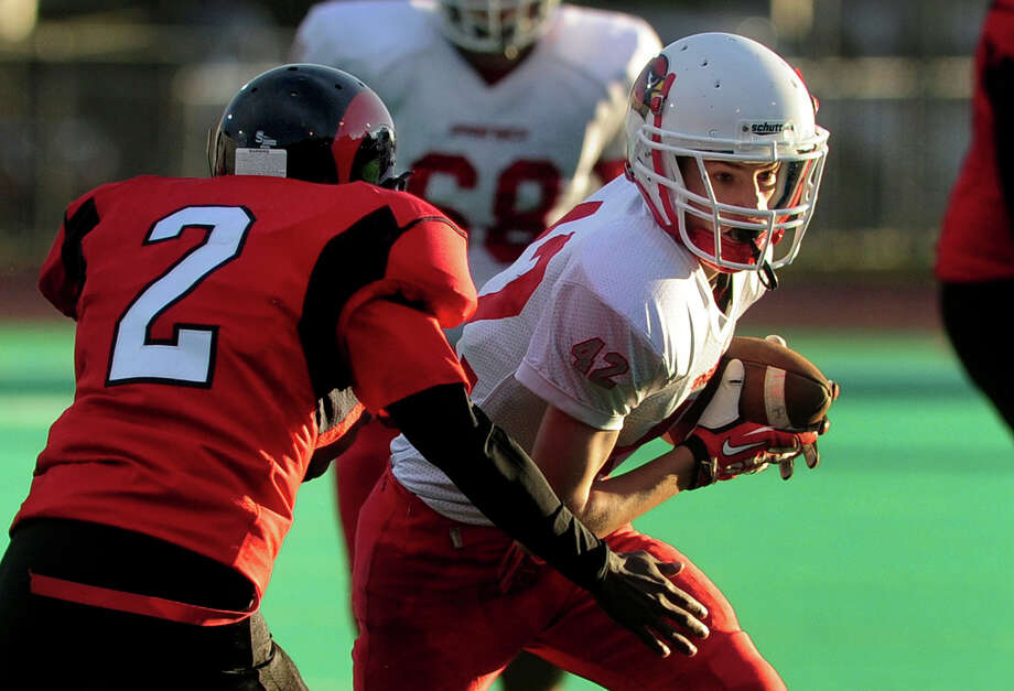 Greenwich's Kevin Piotrzkowski tries to avoid a tackle by Central's Dequan Crawford, during high school football action in Bridgeport, Conn. on Friday November 1, 2013. Photo: Christian Abraham / Connecticut Post