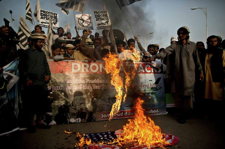 Supporters of the religious party Jamaat-u-Dawa burn an American flag Friday in Islamabad during a rally to condemn U.S. drone attacks, one of which apparently killed Pakistani Taliban chieftan Hakimullah Mehsud. Photo: Muhammed Muheisen, STF / AP