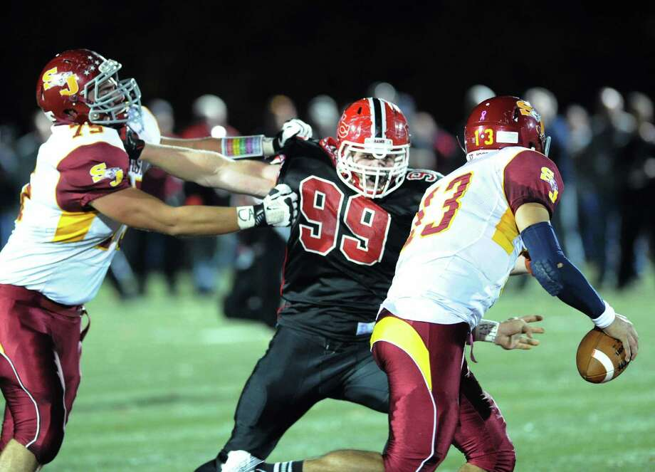 New Canaan's Connor Buck (# 99), at center, holds off St. Joseph blocker, Steve Hashemi (# 75), left, while chasing down St. Joseph quarterback Jordan Vazzano (# 13), right, during the high school football game between New Canaan and St. Joseph at New Canaan, Friday night, Nov. 1, 2013. Photo: Bob Luckey / Greenwich Time