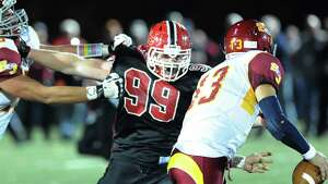 New Canaan's Connor Buck (# 99), at center, holds off St. Joseph blocker, Steve Hashemi (# 75), left, while chasing down St. Joseph quarterback Jordan Vazzano (# 13), right, during the high school football game between New Canaan and St. Joseph at New Canaan, Friday night, Nov. 1, 2013.