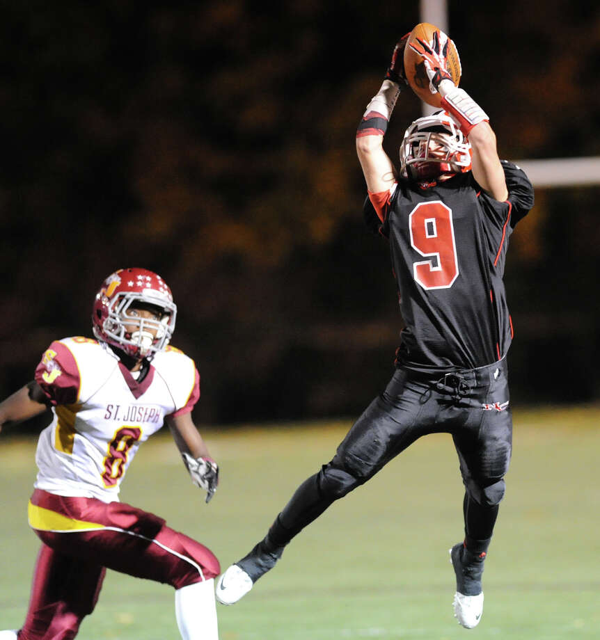 Wide receiver, Cole Turpin (# 9) of New Canaan, right, makes a reception as St. Joseph defender Darren Jackson (#8) looks on during the high school football game between New Canaan and St. Joseph at New Canaan, Friday night, Nov. 1, 2013. Photo: Bob Luckey / Greenwich Time