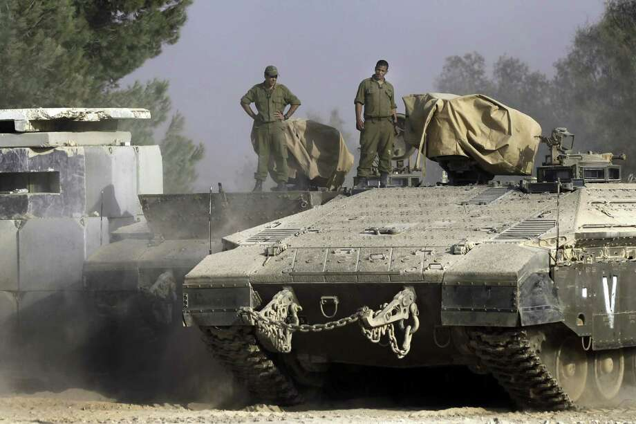 Israelis stand on armored personnel carriers near the Israeli-Gaza border. Five soldiers blowing up a tunnel were wounded by an explosive device. Photo: Tsafrir Abayov / Associated Press
