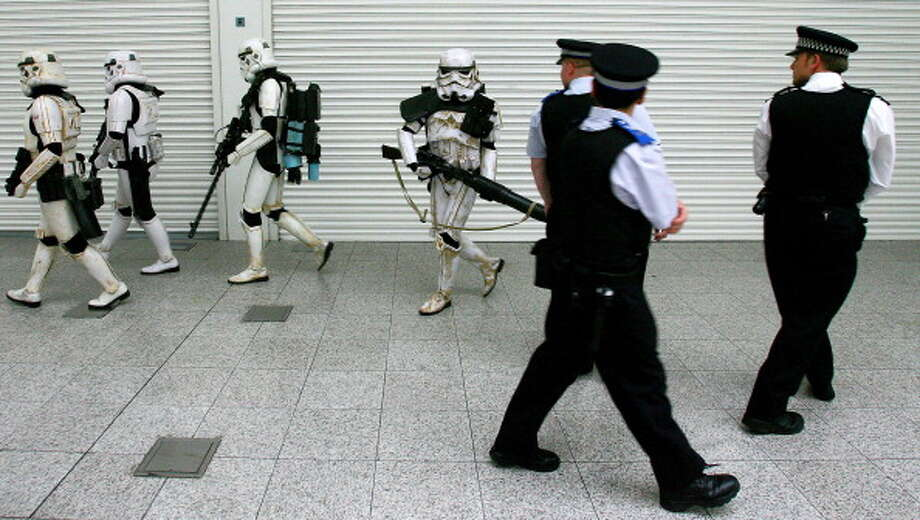 British police officers walk past actors dressed as Stromtroopers from the science fiction film 'Star Wars' during a posed photo opportunity at Star Wars Celebration Europe in London, 13 July 2007. Star Wars Celebration Europe is an event held to comemorate 30 years of Star Wars. Photo: CARL DE SOUZA, Getty Images / 2011 AFP