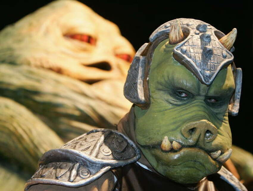 A person in costume as a Gammorean Guard in front of a model of Jabba at the Celebration Europe Exhibition in Excel Centre on July 13 in London, England. The Star Wars Celebration Europe commemorates the first 30 years of the most successful film series to date.