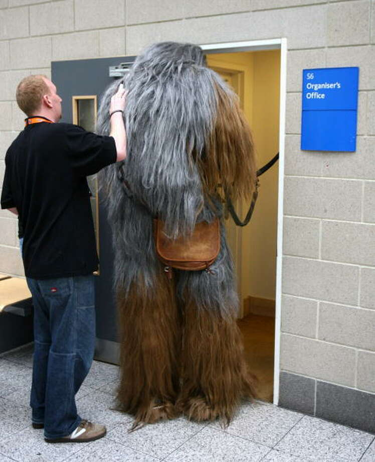 An assistant tries to fit a star wars character into the organiser's office at the Star Wars Celebration Europe in the Excel centre on July 13, 2007 in London, England. The celebration is the largest of its kind in Europe. Photo: Chris Jackson, Getty Images / 2007 Getty Images