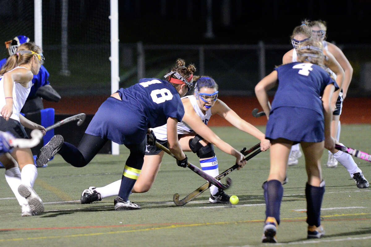 Darien's Mollie Riegel is surrounded by Wilton's Madison Hendry and Maggie Mendola as Wilton High School challenges Darien High School in the FCIAC field hockey finals at Brien McMahon High School in Norwalk, CT on Friday, Nov. 1, 2013.