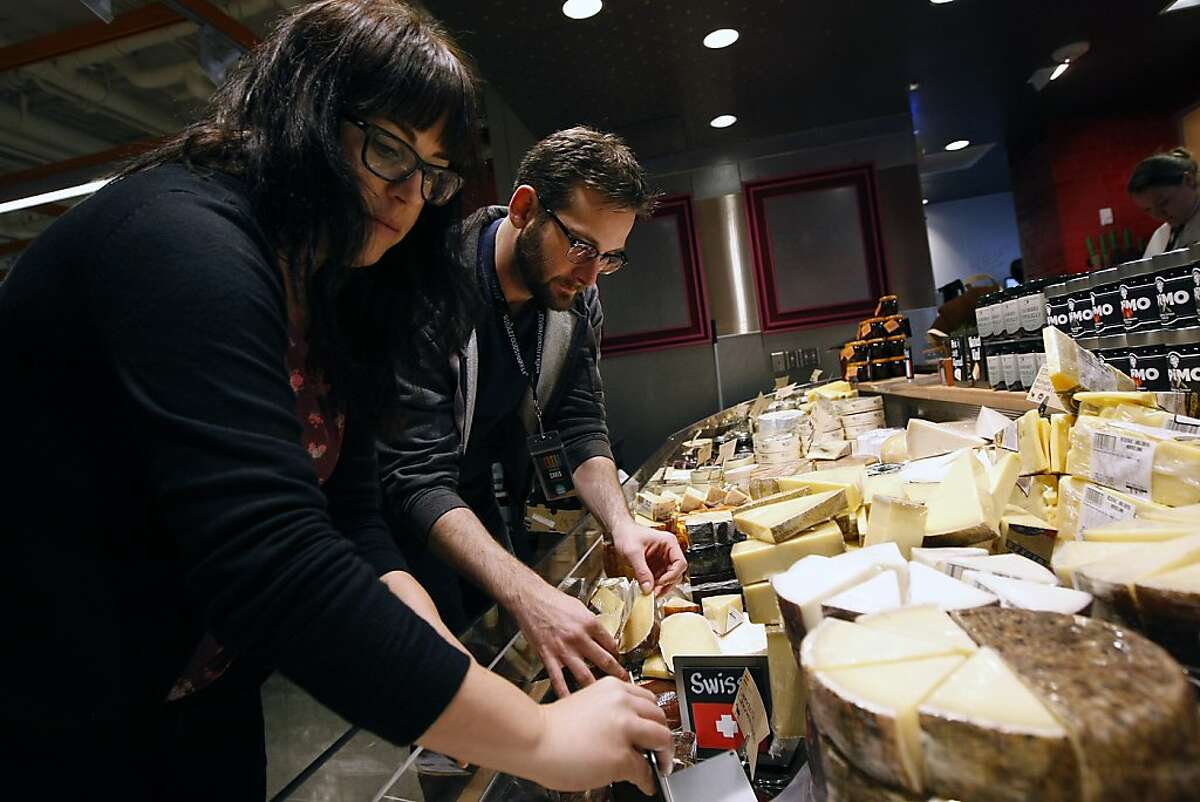 Hayley Gaines, left, and Chris Chandler stock the cheese case as they help prepare for the grand opening of the new Whole Foods Market on the corner of Market St. and Dolores St. in San Francisco, CA Friday, November 1, 2013.