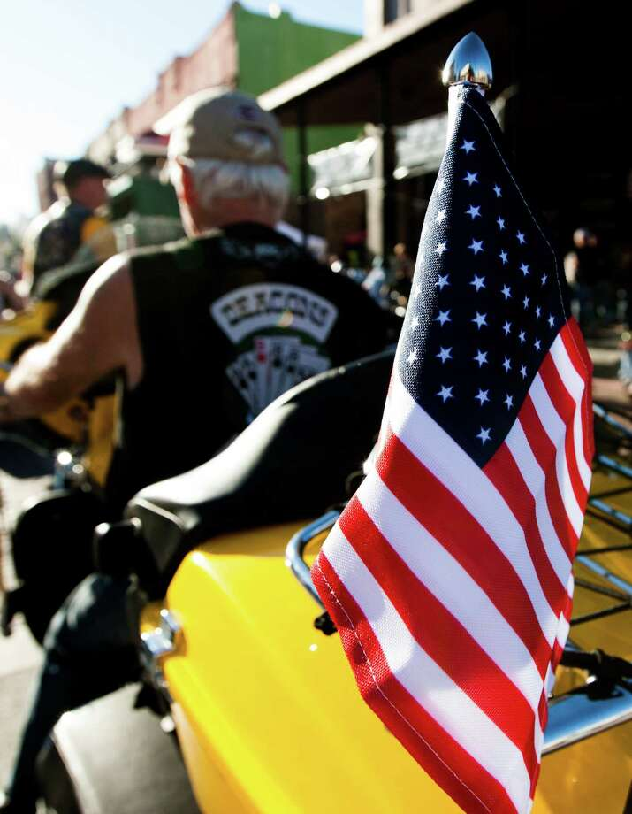 A biker rides with his American Flag attached along the Strand during the 2013 Lone Star Rally on Friday, Nov. 1, 2013, in Galveston. Photo: J. Patric Schneider, For The Chronicle / © 2013 Houston Chronicle