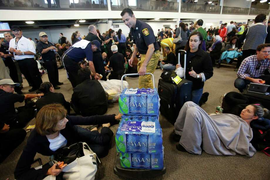 Los Angeles firefighters pass out water to passengers forced to shelter in the international terminal of Los Angeles International Airport. Photo: Eric Kayne / Eric Kayne