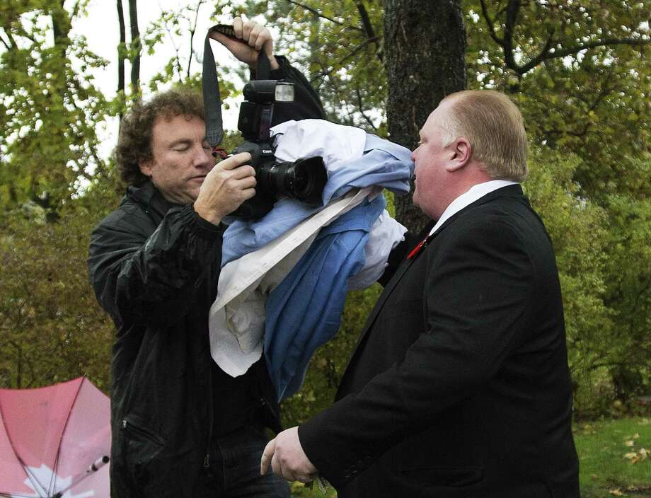 Toronto Mayor Rob Ford (right) pushes a photographer as he leaves his home Thursday. Toronto police said they have a copy of a long-rumored video that appears to show Ford puffing a crack pipe. Ford denied smoking crack and said the video doesn't exist. Photo: Associated Press