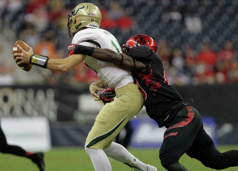 South Florida quarterback Mike White, left, was the latest victim of Derrick Mathews and the revamped Houston defense in Thursday's win for the Cougars. Photo: James Nielsen, Staff / © 2013  Houston Chronicle