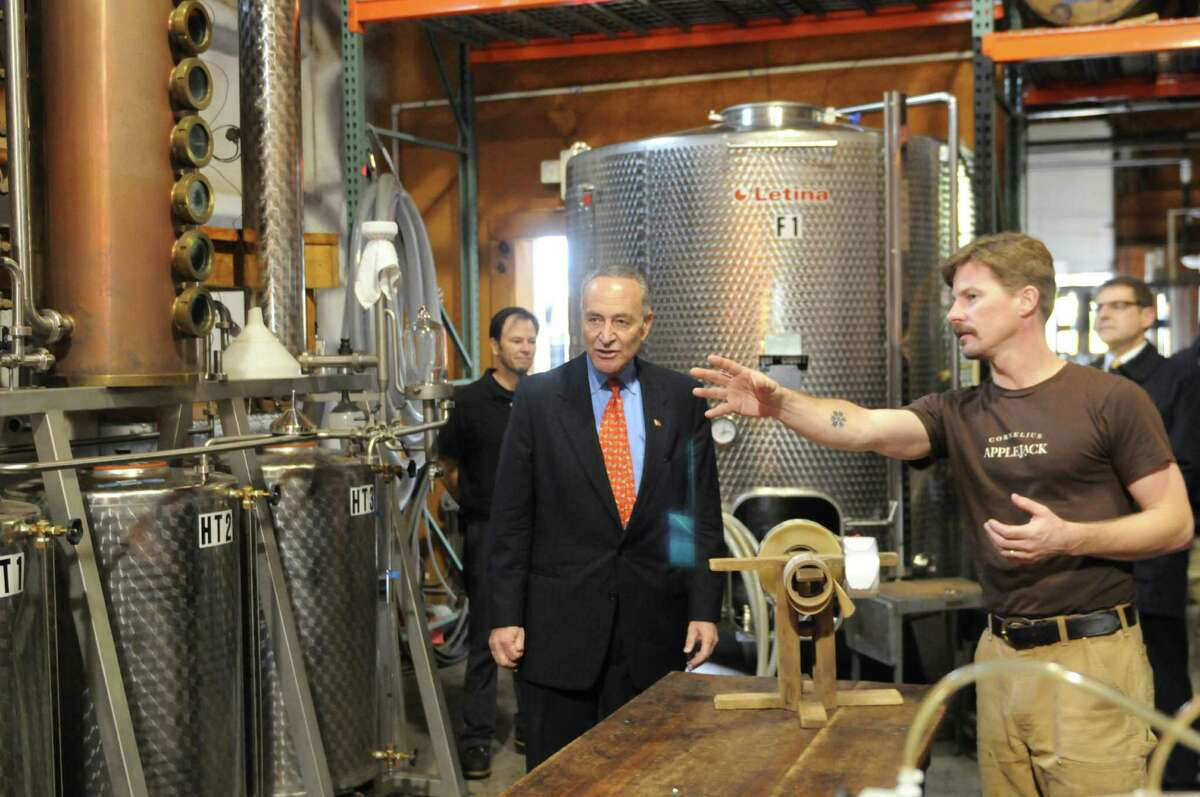 Sen. Charles Schumer is given a tour of Harvest Spirts Distillery by proprietor Derek Grout, right, Friday, Nov. 1, 2013, at Golden Harvest Farms in Valatie, N.Y. Sen. Schumer came to Golden Harvest to promote his CIDER Act legislation, which would lower the tax rate that hard cider is calculated at. The CIDER Act would bring hard cider into the same tax rate as beer. It is currently taxed at a higher rate which is comparative to wine. (Will Waldron/Times Union)