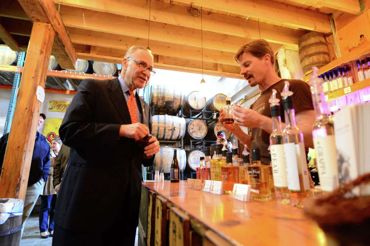 Sen. Charles Schumer samples some of the liquor produced at Harvest Spirts Distillery by proprietor Derek Grout, right, Friday, Nov. 1, 2013, at Golden Harvest Farms in Valatie, N.Y. Sen. Schumer came to Golden Harvest to promote his CIDER Act legislation which would lower the tax rate that hard cider is calculated at. The CIDER Act would bring hard cider into the same tax rate as beer. It is currently taxed at a higher rate which is comparative to wine. (Will Waldron/Times Union)