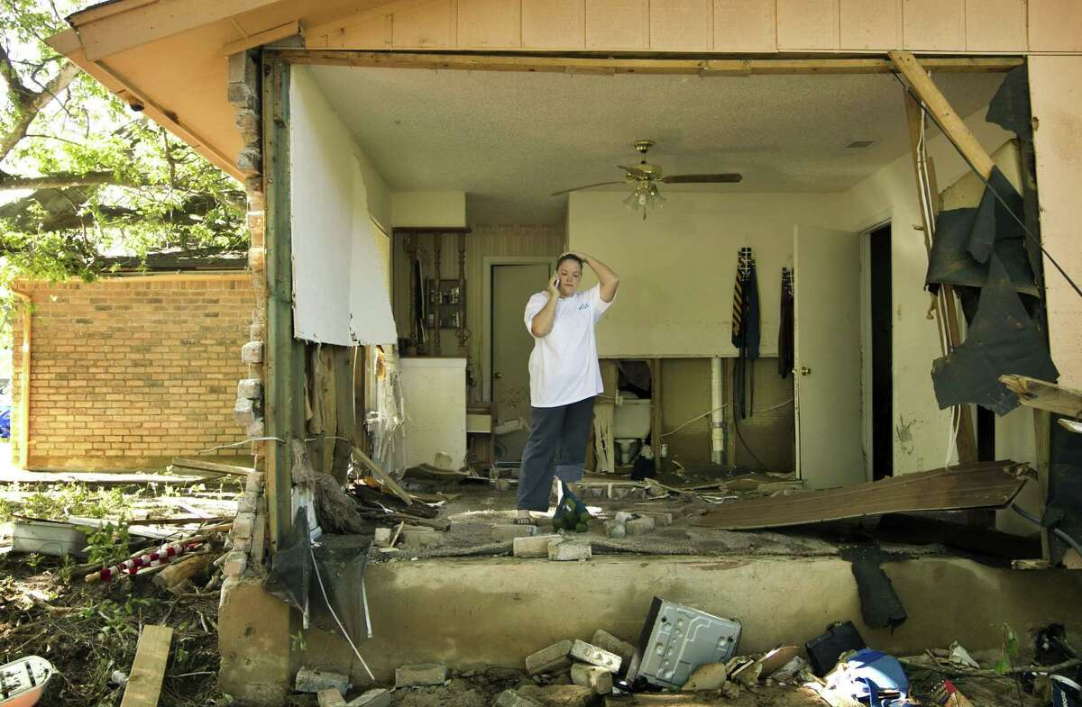 Bene Jacobs-Joiner stands in her bedroom in Austin, Texas, on Friday, November 1, 2013, a day after a flood ripped the wall off her house. She and her husband and their three children made it out safely, but their house and belongings were destroyed.