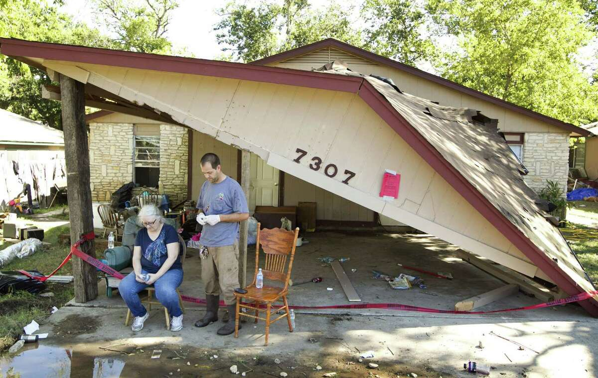 Kim Morris and her son, Robert Morris, take a break from cleaning Robert's home in Austin, Texas, on Friday, November 1, 2013, a day after a flood destroyed the house and his belongings.
