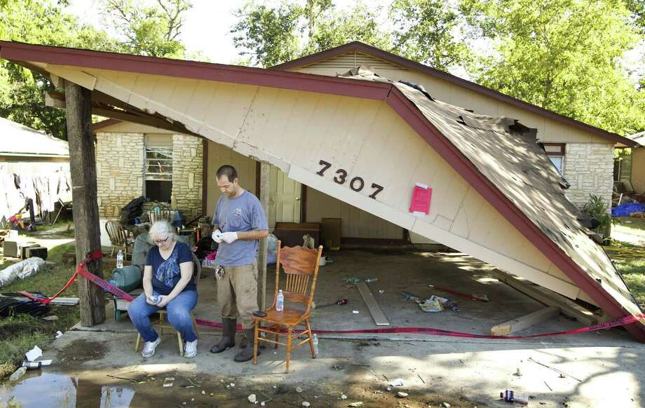 Kim Morris and her son, Robert Morris, take a break from cleaning Robert's home in Austin, Texas, on Friday, November 1, 2013, a day after a flood destroyed the house and his belongings. Photo: Jay Janner, McClatchy-Tribune News Service / Austin American-Statesman