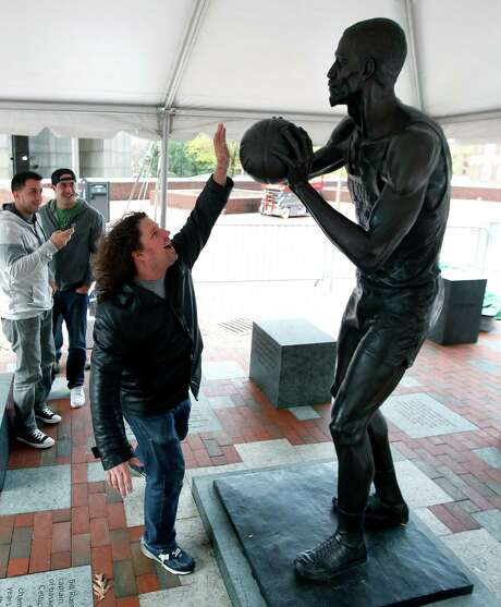 Scott Damgaard strikes a post at the Bill Russell statue at City Hall Plaza in Boston on Friday. Photo: Elise Amendola, STF / AP